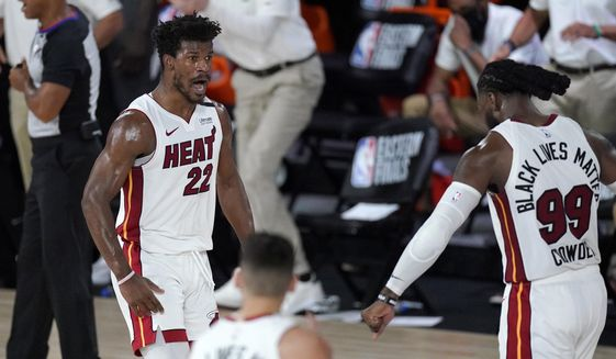Miami Heat's Jimmy Butler (22), Tyler Herro, bottom center, and Jae Crowder (99) celebrate a game tying basket by Butler late in the second half of an NBA conference final playoff basketball game against the Boston Celtics on Tuesday, Sept. 15, 2020, in Lake Buena Vista, Fla. (AP Photo/Mark J. Terrill)  **FILE**