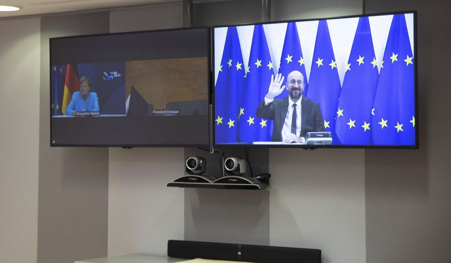 European Council President Charles Michel, screen right, waves as he attends a video conference with German Chancellor Angela Merkel, screen left, and Turkish President Recep Tayyip Erdogan at the European Council building in Brussels, Tuesday, Sept. 22, 2020. (Aris Oikonomou, Pool via AP)