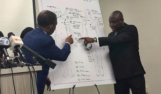 """Attorneys Carl Douglas, left, and Benjamin Crump, right, point to bullet wounds on a diagram of Dijon Kizzee's body as part of an independent autopsy during a news conference in Los Angeles on Tuesday, Sept. 22, 2020. Dijon Kizzee, 29, """"posed no threat"""" to deputies when they fired 19 shots at him, attorney Crump said at the news conference. Kizzee shot and killed by Los Angeles County sheriff's deputies wasn't holding a gun when they opened fire, attorneys for his family said Tuesday, contradicting a claim that he had picked up a dropped weapon during a struggle. (AP Photo/Stefanie Dazio)"""