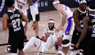 Denver Nuggets' Jamal Murray (27) looks on as Los Angeles Lakers' Anthony Davis (3) grabs his wrist after falling to the floor during play in the second half of Game 3 of the NBA basketball Western Conference final Tuesday, Sept. 22, 2020, in Lake Buena Vista, Fla. (AP Photo/Mark J. Terrill)  **FILE**