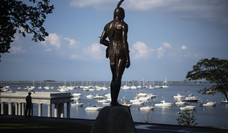 """A statue of the Native Sachem (leader) Massasoit looks out over the traditional point of arrival of the Pilgrims on the Mayflower in 1620, in Plymouth, Mass., Wednesday, Aug. 12, 2020. In the years preceding the Pilgrims' arrival, the Native inhabitants of southern New England had been ravaged by what some scientists refer to as a """"virgin soil"""" epidemic. The unidentified disease, perhaps introduced by European fishermen who plied the waters from Maine to Narragansett Bay, burned through village after village, killing up to 90 percent of some tribes. (AP Photo/David Goldman)"""