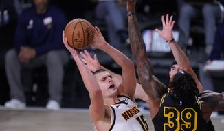 Denver Nuggets' Nikola Jokic (15) shoots over Los Angeles Lakers' Dwight Howard (39) during the first half of an NBA conference final playoff basketball game Sunday, Sept. 20, 2020, in Lake Buena Vista, Fla. (AP Photo/Mark J. Terrill)