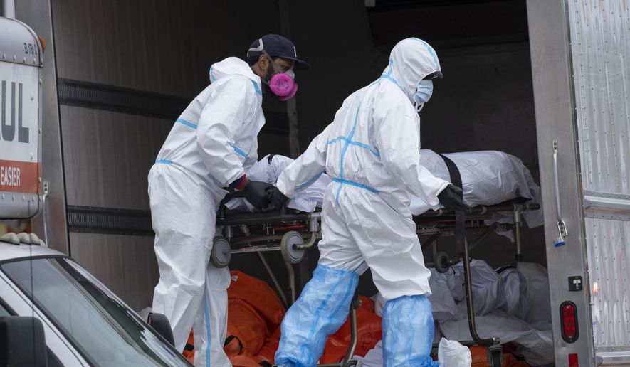 In this April 29, 2020, file photo, workers move bodies to a refrigerated truck from the Andrew T. Cleckley Funeral Home in the Brooklyn borough of New York. During the deadliest days of the coronavirus outbreak in New York City, the bodies piled up at the funeral home — and the stench that came with it — at an alarming rate. Cleckley says what happened next made him the scapegoat for an unforeseen crisis — hundreds of COVID-19 deaths a day in New York that overwhelmed funeral homes across the city. Authorities swept in and suspended his license in an episode that made headlines in a city already reeling from other horrors of the pandemic. (AP Photo/Craig Ruttle) ** FILE **