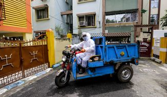 A civic staff in protective suit arrives to disinfect an apartment where one of the residents tested positive for COVID-19  in Kolkata, India, Tuesday, Sept. 22, 2020. The nation of 1.3 billion people is expected to become the coronavirus pandemic's worst-hit country within weeks, surpassing the United States. (AP Photo/Bikas Das)