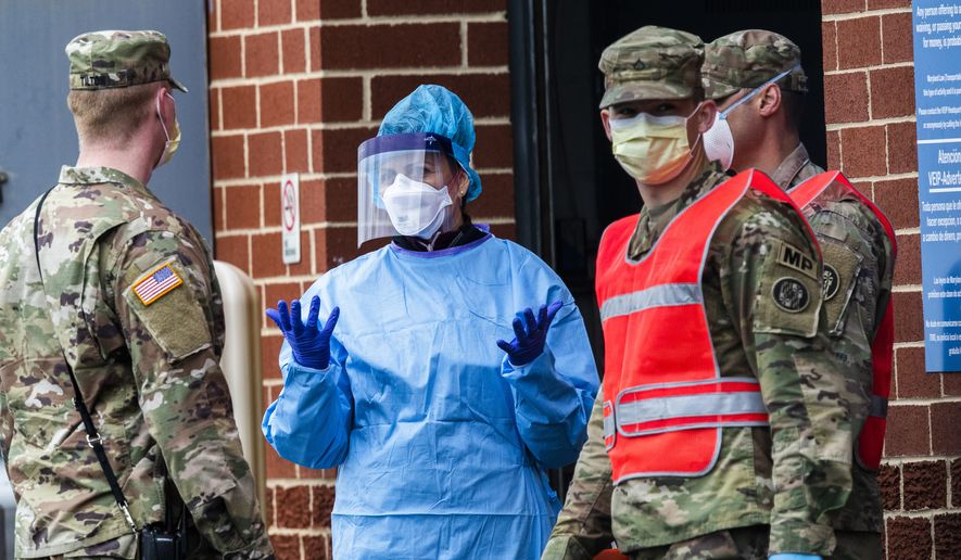 Medical personnel from Montgomery County, Md., talks to members of the Army National Guard assisting in the drive-in testing of COVID-19 patients in Silver Spring, Md., Tuesday, April 21, 2020. (AP Photo/Manuel Balce Ceneta) ** FILE **