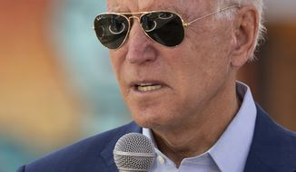 Social distancing circles are reflected int he the sunglasses of Democratic presidential candidate former Vice President Joe Biden as he speaks during a Biden for President Black economic summit at Camp North End in Charlotte, N.C., Wednesday, Sept. 23, 2020. (AP Photo/Carolyn Kaster)