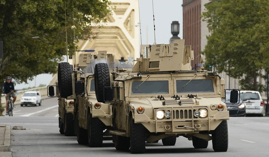 Four wheeled military vehicles enter the city ahead of a 9:00 pm curfew, Wednesday, Sept. 23, 2020, in Louisville, Ky. A grand jury has indicted one officer on criminal charges six months after Breonna Taylor was fatally shot by police in Kentucky. The jury presented its decision against fired officer Brett Hankison Wednesday to a judge in Louisville, where the shooting took place. (AP Photo/Darron Cummings)