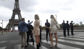Russian tourists, one holding a bottle of Champagne, talk to police officers securing the bridge leading to the Eiffel Tower, Wednesday, Sept. 23, 2020 in Paris. Paris police have blockaded the area around the Eiffel Tower after a phone-in bomb threat. (AP Photo/Michel Euler)