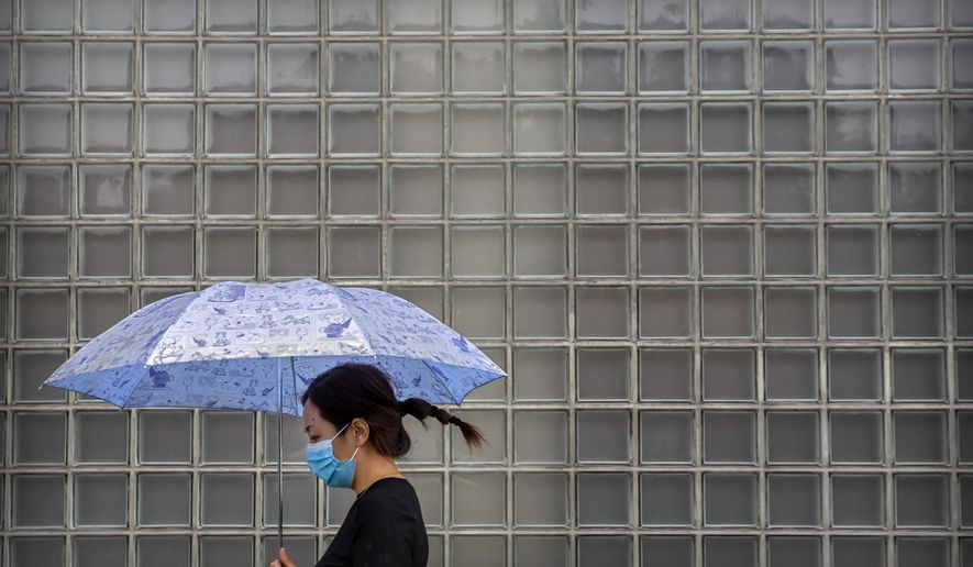 A woman wearing a face mask to protect against the coronavirus walks past a shopping mall on a rainy day in Beijing, Wednesday, Sept. 23, 2020. Even as China has largely controlled the outbreak, the coronavirus is still surging across other parts of the world. (AP Photo/Mark Schiefelbein)
