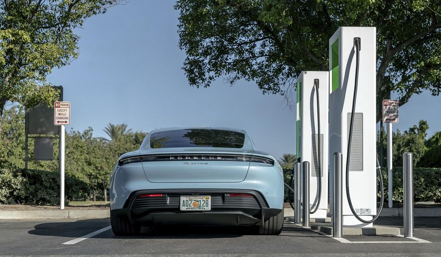 This photo provided by Porsche shows its first all-electric production car, the 2020 Taycan, charging up at a public charging station. Its official range according to the EPA is 203 miles on a single charge, but in Edmunds' testing the Taycan showed it's capable of going over 100 additional miles. (Courtesy of Porsche Cars North America via AP)