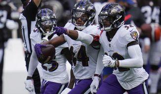 Baltimore Ravens cornerback Marlon Humphrey (44) celebrates after intercepting a pass, during an NFL football game against the Cleveland Browns, Sunday, Sept. 13, 2020, in Baltimore. To the right Baltimore Ravens safety DeShon Elliott (32) and cornerback Tavon Young (25), left. (AP Photo/Julio Cortez)