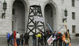 FILE - In this Feb. 6, 2015, file photo, protesters prepare to take down a makeshift oil derrick that was set up in front of the California State Office Building to protest fracking in San Francisco. California Gov. Gavin Newsom moved Wednesday, Sept. 23, 2020, to end issuing new hydraulic fracturing permits by 2024, a delay criticized by many environmental groups but characterized as legally and politically realistic by another. (AP Photo/Jeff Chiu, File)