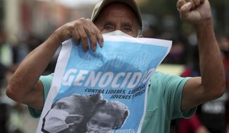 "A protester holds a poster with a message that reads in Spanish: ""Stop the Genocide,"" during a demonstration against a wave of massacres, in Bogota, Colombia, Monday, Sept. 21, 2020. Rather than a national dispute between guerrillas and the state, violence in rural Colombia is now marked by a patchwork of local feuds between criminal groups who fight over drug routes, illegal mines and even gasoline smuggling routes. (AP Photo/Fernando Vergara)"
