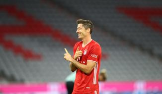 Bayern's Robert Lewandowski, celebrates after scoring a goal with a penalty kick, during the German Bundesliga soccer match between FC Bayern Munich and Schalke 04 in Munich, Germany, Friday, Sept. 18, 2020. (AP Photo/Matthias Schrader)