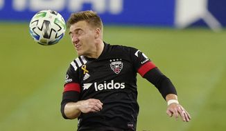 D.C. United midfielder Julian Gressel (31) heads the ball away from Nashville SC defender Taylor Washington, right, during the first half of an MLS soccer match Wednesday, Sept. 23, 2020, in Nashville, Tenn. (AP Photo/Mark Humphrey)  **FILE**