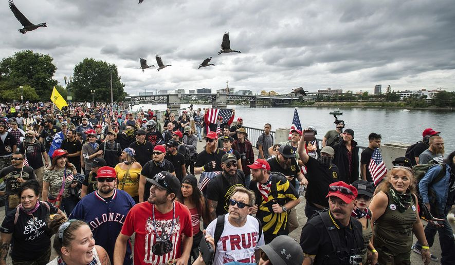 In this Aug. 17, 2019, file photo, members of the Proud Boys and other right-wing demonstrators march along the Willamette River during a rally in Portland, Ore. (AP Photo/Noah Berger, File)