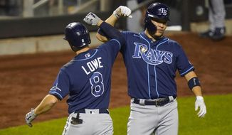 Tampa Bay Rays' Brandon Lowe, left, celebrates with teammate Yoshitomo Tsutsugo, of Japan, after they scored on a two-run home run by Lowe during the eighth inning of a baseball game against the New York Mets Wednesday, Sept. 23, 2020, in New York. (AP Photo/Frank Franklin II)