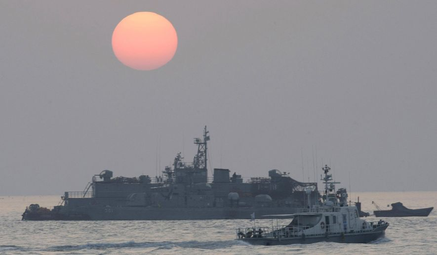 In this Dec. 22, 2010, file photo, a government ship sails past the South Korean Navy's floating base as the sun rises near Yeonpyeong island, South Korea. A South Korean official who disappeared off a government ship near the disputed sea boundary with North Korea this week may be in North Korea, South Korea's Defense Ministry said Wednesday, Sept. 23, 2020. (AP Photo/Ahn Young-joon, File)