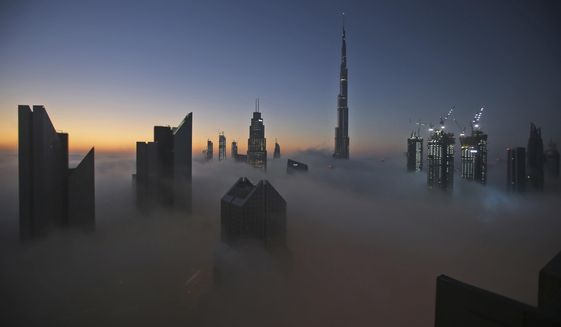 FILE - In this Dec. 31, 2016 file photo, the sun rises over the city skyline with the Burj Khalifa, the world's tallest building, on a foggy day in Dubai, United Arab Emirates. Dubai is tapping the global financial market to potentially raise billions of dollars for the first time in years. That's according to a bond prospectus seen on Tuesday, Sept. 1, 2020, by The Associated Press. It reveals the deepening toll of the coronavirus pandemic on Dubai's economy. (AP Photo/Kamran Jebreili, File)