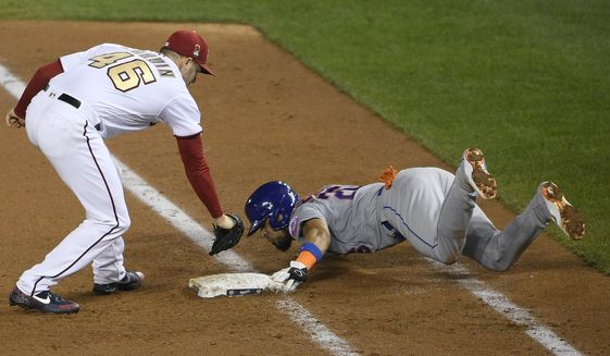 New York Mets' Robinson Chirinos, right, slides safely into first against Washington Nationals starting pitcher Patrick Corbin (46) during the sixth inning of a baseball game, Thursday, Sept. 24, 2020, in Washington. The Mets won 3-2. (AP Photo/Nick Wass)  **FILE**