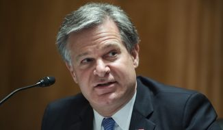 """FBI Director Christopher Wray testifies during a Senate Homeland Security and Governmental Affairs Committee hearing on """"Threats to the Homeland"""" Thursday, Sept. 24, 2020, on Capitol Hill in Washington. (Tom Williams/Pool via AP) ** FILE **"""