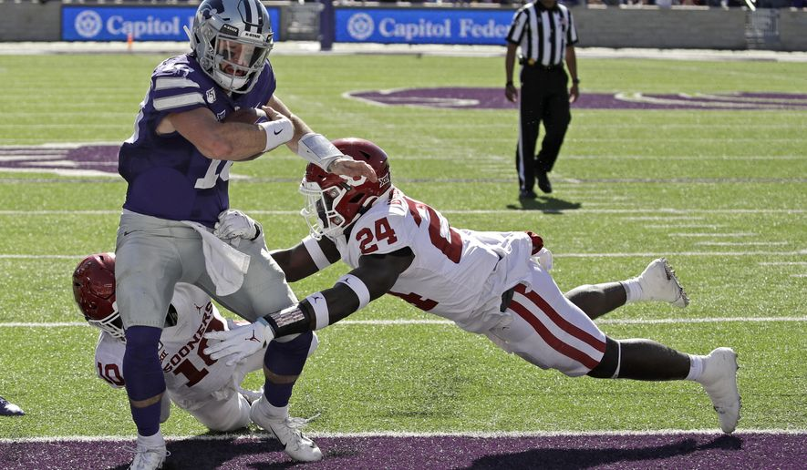 FILE - In this Oct. 26, 2019, file photo, Kansas State quarterback Skylar Thompson (10) runs into the end zone to score a touchdown as Oklahoma linebacker Brian Asamoah (24) and safety Pat Fields (10) defend during the second half of an NCAA college football game in Manhattan, Kan. Kansas State won 48-41. Thompson is now set to make his 29th career start when the Wildcats try to only their fifth win ever over a top-five team, this week against Oklahoma. This matchup will be in Norman. (AP Photo/Charlie Riedel, File)