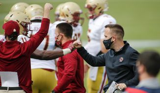 Boston College head coach Jeff Hafley, right, fistbumps a player on the sideline in the second half of an NCAA college football game against Duke, Saturday, Sept. 19, 2020, in Durham, N.C. (Nell Redmond/Pool Photo via AP)