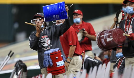 Members of the Reds' grounds crew acknowledge Cincinnati Reds' Trevor Bauer as he stands in the dugout in the ninth inning during a baseball game between the Milwaukee Brewers and the Cincinnati Reds in Cincinnati, Wednesday, Sept. 23, 2020. The Reds won 6-1. (AP Photo/Aaron Doster)  **FILE**