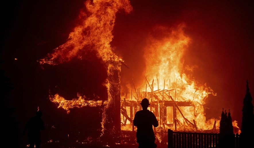 In this Nov. 8, 2018, file photo, a home burns as the Camp Fire rages through Paradise, Calif. (AP Photo/Noah Berger, File)