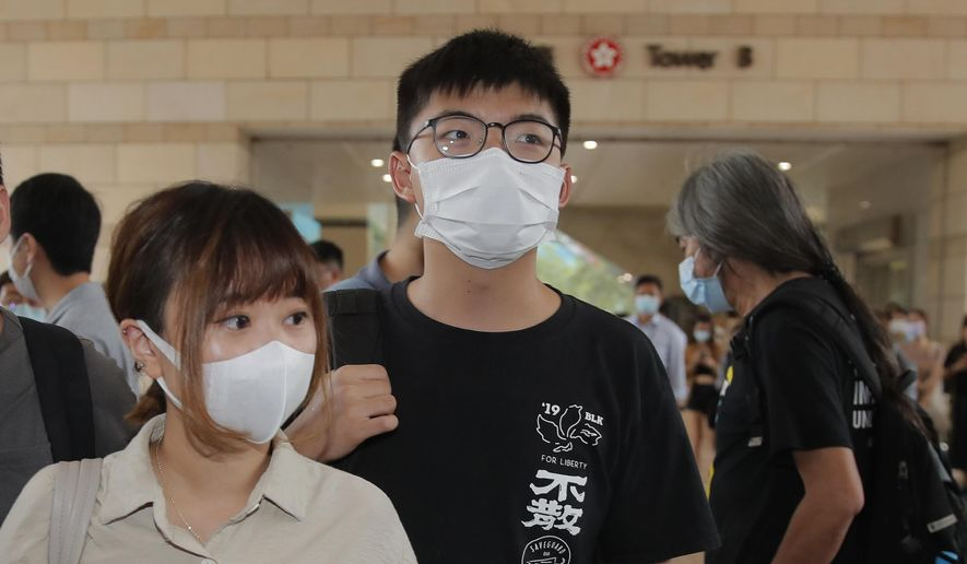 Various of groups of pro-democracy activists including Joshua Wong, center, arrive at a court in Hong Kong, Tuesday, Sept. 15, 2020. Prominent activists Jimmy Lai and Joshua Wong were among more than two dozen activists appearing in court after being charged of participating in unlawful assembly. They were charged for joining a vigil last June 4 to commemorate the anniversary of the 1989 Tiananmen crackdown. While the event has been held every year, authorities did not grant permission for the gathering this year citing concerns over the spread of coronavirus. (AP Photo/Kin Cheung)