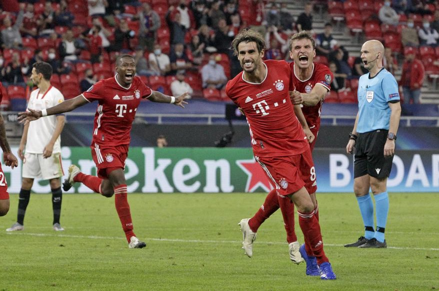 Bayern's Javi Martinez, center, celebrates with teammates after scoring his side's second goal during the UEFA Super Cup soccer match between Bayern Munich and Sevilla at the Puskas Arena in Budapest, Hungary, Thursday, Sept. 24, 2020. (Bernadett Szabo/Pool via AP)