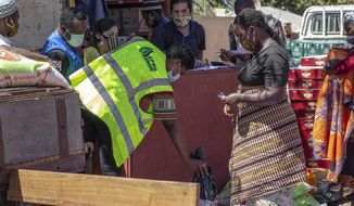 In this handout photo provided by the World Food Program on Tuesday, Sept. 22, 2020, a woman collects a monthly food parcel in Cabo Delgado Province, Mozambique, Thursday, Aug. 27, 2020. The WFP says the escalating extremist insurgency in northern Mozambique has displaced 310,000 people, creating an urgent humanitarian crisis. (Falume Bachir/World Food Program via AP)