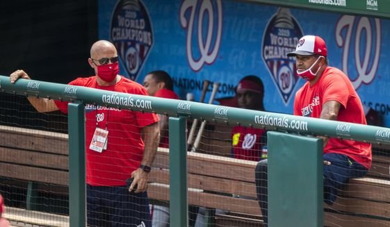 In this Sunday, Aug. 2, 2020, file photo, Washington Nationals manager Dave Martinez, right, with General Manager Mike Rizzo, left, watch from the dugout a baseball intrasquad game at Nationals Park in Washington. For the second season in a row, manager Dave Martinez's Washington Nationals got off to a 19-31 start. This time, there were not enough games to dig themselves out of that hole. (AP Photo/Manuel Balce Ceneta, File)  **FILE**
