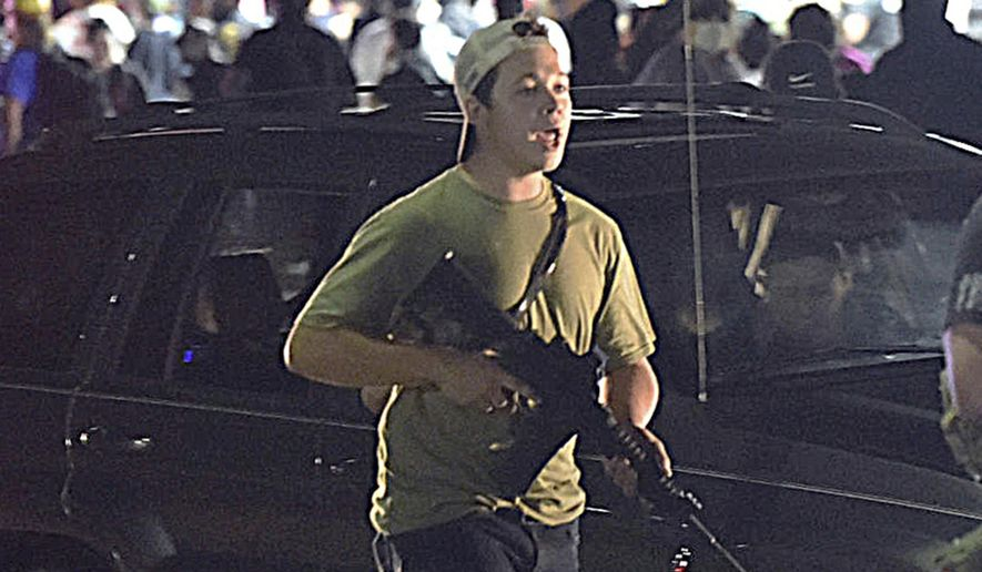 In this Tuesday, Aug. 25, 2020, file photo, Kyle Rittenhouse carries a weapon as he walks along Sheridan Road in Kenosha, Wis., during a night of unrest following the weekend police shooting of Jacob Blake. The way his lawyers tell it, the teenager wasn't a scared, gun enthusiast in over his head when he fatally shot two protesters. He was a courageous defender of liberty, a patriot exercising his right to bear arms amid chaos in the streets. But some legal experts say Rittenhouse's lawyers are taking big risks by turning a fairly straightforward self-defense case into a sweeping political argument that mirrors the law-and-order re-election campaign of President Donald Trump. (Adam Rogan/The Journal Times via AP) ** FILE **