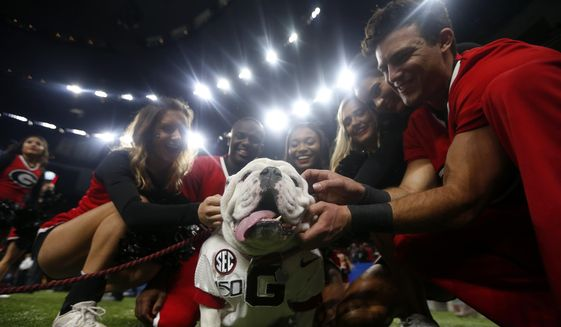 "Georgia cheerleaders pose with the school mascot ""Uga"" before the Sugar Bowl NCAA college football game against Baylor in New Orleans, Wednesday, Jan. 1, 2020. Football is being played in the Power Five conferences, but many of the longstanding traditions that go along with the games are on hold during the pandemic. Georgia's white English bulldog Uga and other live animal mascots won't be in SEC stadiums because of the conference's precautions against coronavirus. (AP Photo/Brett Duke, file)  **FILE**"