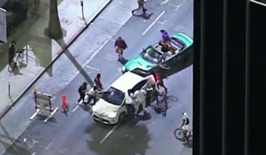 Black Lives Matter activists attempt to pull a driver from his vehicle after the individual attempted to avoid their human street blockade, Sept. 24, 2020. (Image: NBC News video screenshot)