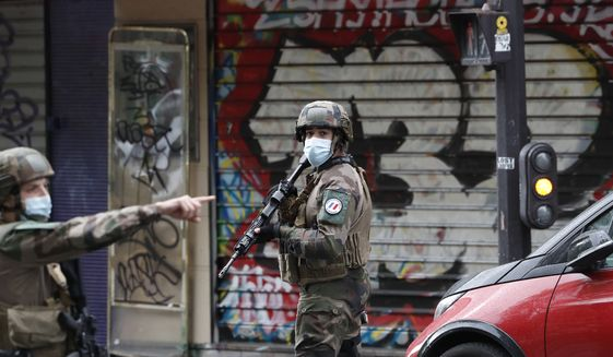 """French soldiers patrol after four people have been wounded in a knife attack near the former offices of satirical newspaper Charlie Hebdo, Friday Sept. 25, 2020 in Paris. A police official said officers are """"actively hunting"""" for the perpetrators and have cordoned off the area including the former Charlie Hebdo offices after a suspect package was noticed nearby. Islamic extremists attacked the offices in 2015, killing 12 people. (AP Photo/Thibault Camus)"""
