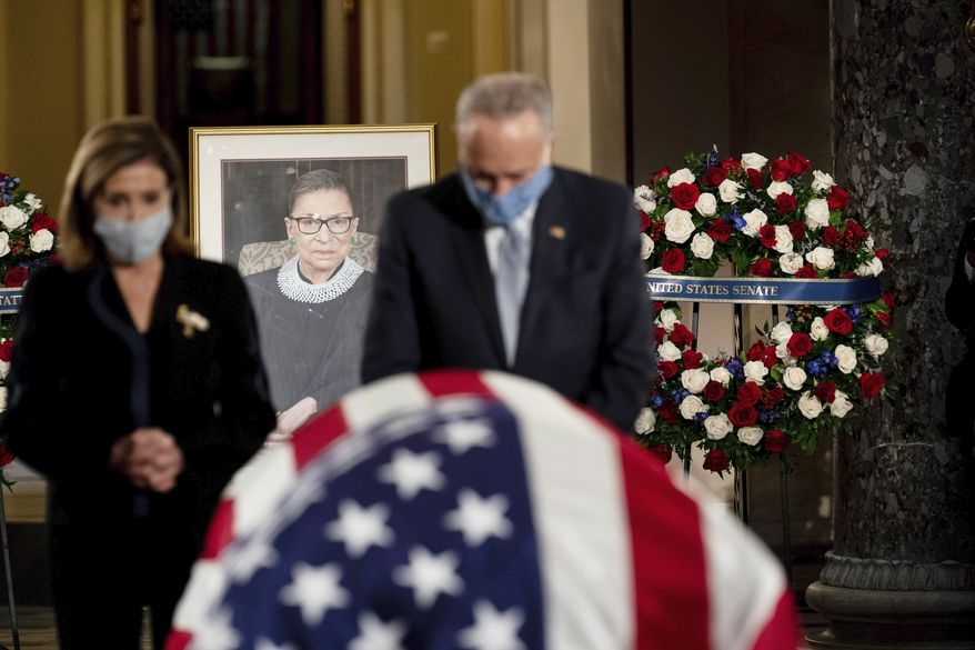 House Speaker Nancy Pelosi and Senate Minority Leader Chuck Schumer, pay their respects to  Justice Ruth Bader Ginsburg as she lies in state in the U.S. Capitol on Friday, Sept. 25, 2020. Ginsburg died at the age of 87 on Sept. 18 and is the first women to lie in state at the Capitol. (Erin Schaff/The New York Times via AP, Pool)