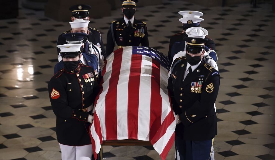 The flag-draped casket of Justice Ruth Bader Ginsburg is carried out by a joint services military honor guard after lying in state at the U.S. Capitol, Friday, Sept. 25, 2020, in Washington.  (Olivier Douliery/Pool via AP)