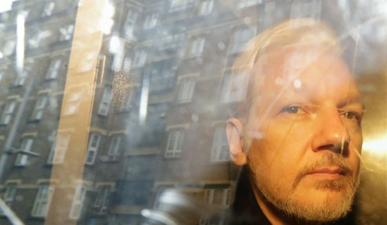 In this Wednesday, May 1, 2019, file photo, buildings are reflected in the window as WikiLeaks founder Julian Assange is taken from court, where he appeared on charges of jumping British bail seven years ago, in London. (AP Photo/Matt Dunham, File)