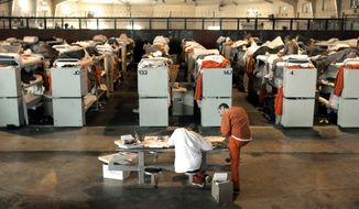 FILE - In this Aug. 3, 2006, file photo, inmates are housed in three tier bunks, in what was once a multi-purpose recreation room, at the Deuel Vocational Institute in Tracy, Calif. California next year will close the prison holding about 1,500 male inmates, Gov. Gavin Newsom's administration said Friday, Sept. 25, 2020, in its latest step to reduce the state's incarceration footprint partly in response to the coronavirus and massive related budget cuts. Shuttering the Deuel Vocational Institution will save about $182 million annually, state corrections officials said. (AP Photo/Rich Pedroncelli, File)