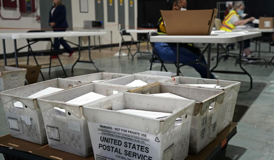 Workers prepare absentee ballots for mailing at the Wake County Board of Elections in Raleigh, N.C., Thursday, Sept. 3, 2020. North Carolina is scheduled to begin sending out more than 600,000 requested absentee ballots to voters on Friday. (AP Photo/Gerry Broome)