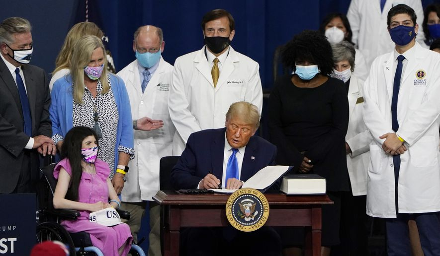 President Donald Trump signs an executive order after delivering remarks on healthcare at Charlotte Douglas International Airport, Thursday, Sept. 24, 2020, in Charlotte, N.C. (AP Photo/Chris Carlson)