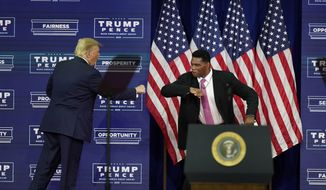 President Donald Trump elbow bumbs with Herschel Walker during a campaign rally, Friday, Sept. 25, 2020, in Atlanta. (AP Photo/John Bazemore)