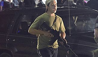 FILE - In this Tuesday, Aug. 25, 2020 file photo, Kyle Rittenhouse carries a weapon as he walks along Sheridan Road in Kenosha, Wis., during a night of unrest following the weekend police shooting of Jacob Blake. Rittenhouse, a 17-year-old accused of killing two protesters days after Jacob Blake was shot by police in Kenosha, Wisconsin, faces a hearing Friday, Sept. 25, 2020 on whether he should be sent to Wisconsin to stand trial on homicide charges that could put him in prison for life. (Adam Rogan/The Journal Times via AP, File)