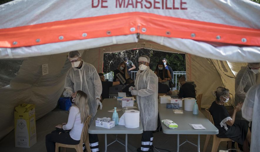 People receive COVID-19 tests at a mobile testing center in Marseille, France, Thursday Sept. 24, 2020. French Health Minister Olivier Veran announced the closure of all restaurants and bars in the Marseille region and restrictions across a dozen other cities to stem the resurgent spread of the virus. With COVID-19 patients now occupying more than 10% of France's intensive care beds, Veran stopped short of imposing new lockdowns, but urged people to resume working from home and stop gathering with big groups of family and friends. (AP Photo/Daniel Cole)