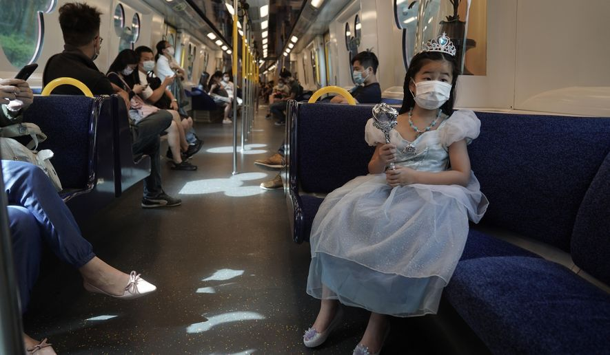 A visitor wearing a face mask rides on a train towards the Hong Kong Disneyland, Friday, Sept. 25, 2020. Hong Kong Disneyland reopened its doors to visitors after closed temporarily due to the coronavirus outbreak. (AP Photo/Kin Cheung)
