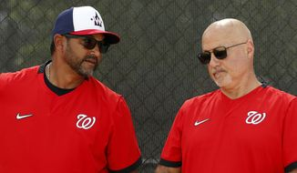 In this Feb. 17, 2020, file photo, Washington Nationals manager Dave Martinez, left, talks with general manager Mike Rizzo during spring training baseball practice in West Palm Beach, Fla. Martinez and the Nationals agreed to a multiyear contract extension that the team announced Saturday, Sept. 26, 2020. (AP Photo/Jeff Roberson, File)  **FILE**