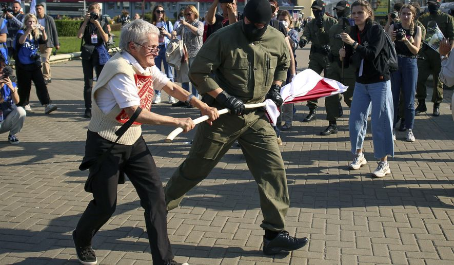 A police officer tries to take away an old Belarusian national flag from Nina Bahinskaya's hands during an opposition rally to protest the official presidential election results in Minsk, Belarus, Saturday, Sept. 26, 2020. Hundreds of thousands of Belarusians have been protesting daily since the Aug. 9 presidential election. (AP Photo/TUT.by)