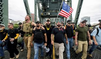 In this Aug. 17, 2019, file photo, members of the Proud Boys and other right-wing demonstrators march across the Hawthorne Bridge during a rally in Portland, Ore. (AP Photo/Noah Berger, File)